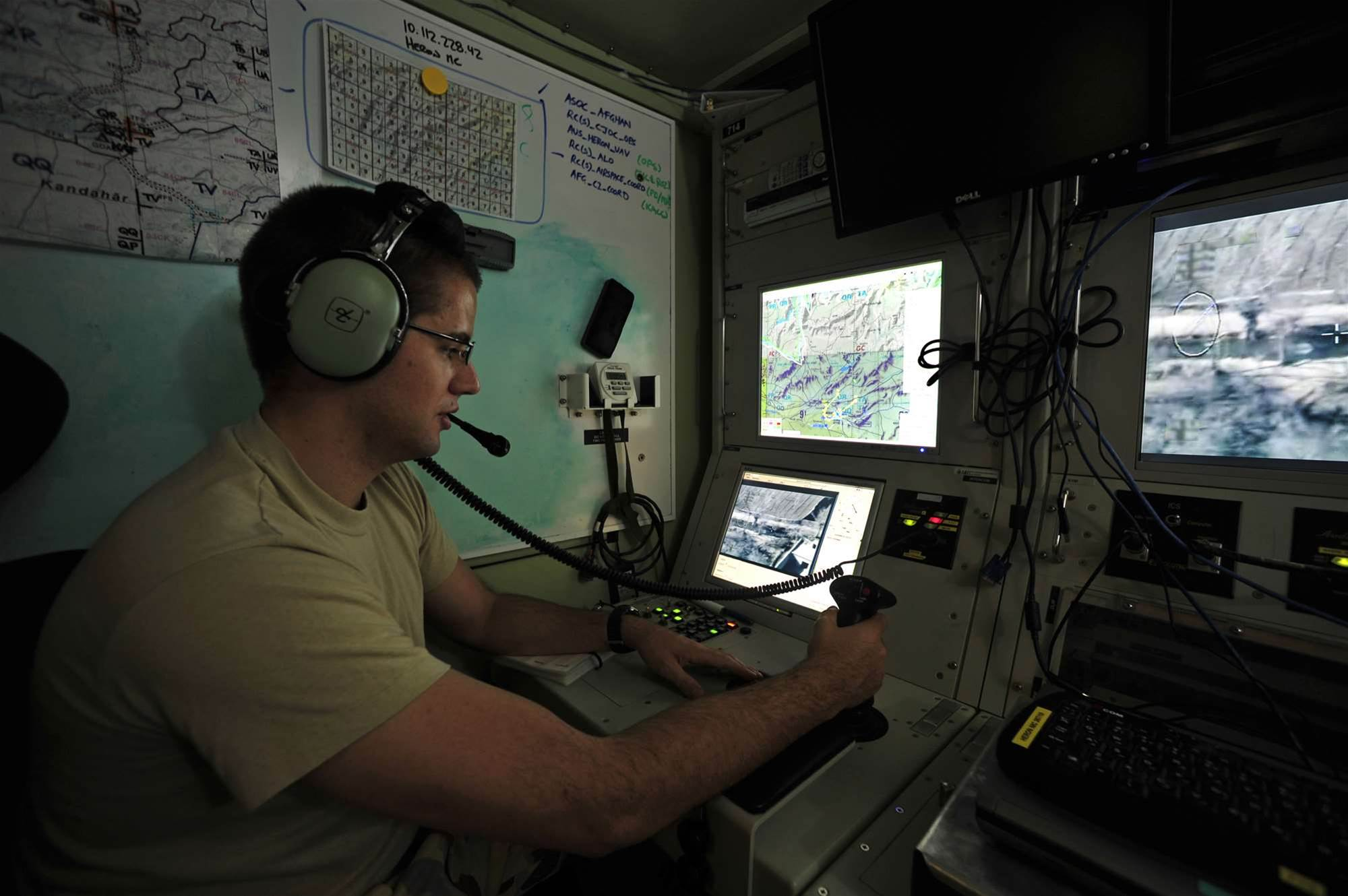 Flying Officer and Heron RPA Payload Operator Aaron Thorpe controls the Heron's surveillance cameras from Ground Control Section – Operation Bay. The Heron carries a combination of sensors that communicate with the ground control station in real time. Credit: Department of Defence.