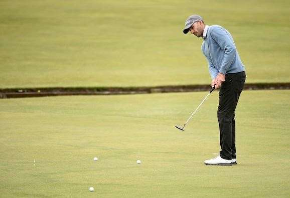 Ogilvy gets in some putting practice on the 1st green at St Andrews yesterday. PHOTO: Getty Images.