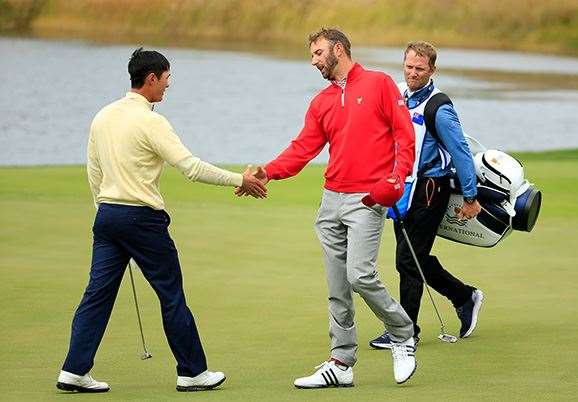Danny Lee shakes hands with Dustin Johnson  after being beaten 2 & 1. PHOTO: David Cannon/Getty Images.