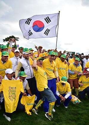 Bae Sang-Moon of South Korea poses with the International Team supporters on the 18th hole after the final round singles matches at the 2015 Presidents Cup. PHOTO: Jung Yeon-Je/AFP/Getty Images.