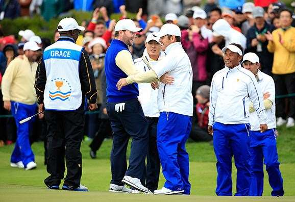 Branden Grace celebrates his 2 & 1 victory with Louis Oosthuizen.  PHOTO: David Cannon/Getty Images.