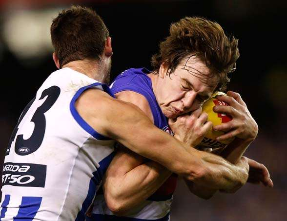 MELBOURNE, AUSTRALIA - AUGUST 29: Liam Picken of the Bulldogs is tackled by Sam Gibson of the Kangaroos during the 2015 AFL round 22 match between the North Melbourne Kangaroos and the Western Bulldogs at Etihad Stadium, Melbourne, Australia on August 29, 2015. (Photo by Michael Willson/AFL Media/Getty Images)