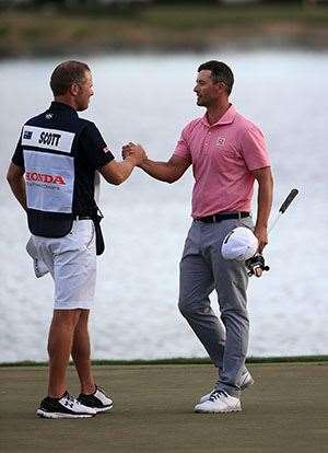 Adam Scott embraces his caddie David Clark after his one shot win at the Honda Classic. PHOTO: Sam Greenwood/Getty Images.