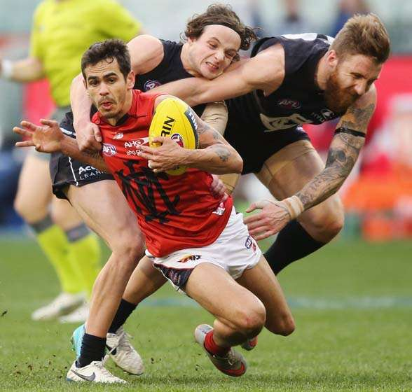 MELBOURNE, AUSTRALIA - AUGUST 23: Jeff Garlett of the Demons is tackled by Dylan Buckley and Zach Tuohy (R) of the Blues during the round 21 AFL match between the Carlton Blues and the Melbourne Demons at Melbourne Cricket Ground on August 23, 2015 in Melbourne, Australia. (Photo by Michael Dodge/Getty Images)