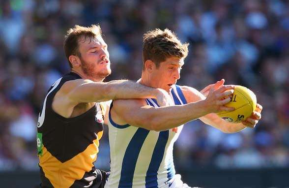 MELBOURNE, AUSTRALIA - SEPTEMBER 13: Nick Dal Santo of the Kangaroos marks infront of Kamdyn McIntosh of the Tigers during the First AFL Elimination Final match between the Richmond Tigers and the North Melbourne Kangaroos at Melbourne Cricket Ground on September 13, 2015 in Melbourne, Australia. (Photo by Quinn Rooney/Getty Images)