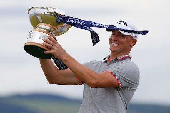 Alex Noren poses with the trophy in high winds at Castle Stuart. PHOTO: Kevin C. Cox/Getty Images.