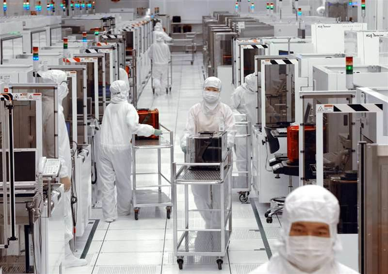 Tainan, TAIWAN: Engineers of United Microelectronics Corp (UMC) push trollies with front opening universal pod (FOUP), containing 25-piece wafers inside, at the 12-inch UMC wafer factory in Tainan Science Park, southern Taiwan, 28 April 2006. UMC, the world's second largest contract microchip maker, said 26 April its net earnings in the first quarter in 2006 rose sharply due to higher non-operating income. UMC is a world-leading semiconductor foundry, specializing in the contract manufacturing of customer designed ICs for high performance semiconductor applications. SAM YEH/AFP/Getty Images