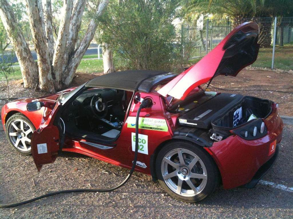 A strange procession as Telsa Roadster and Holden Sportwagon take on Australian outback