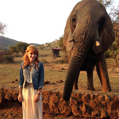 Bella stands next to an Elephant