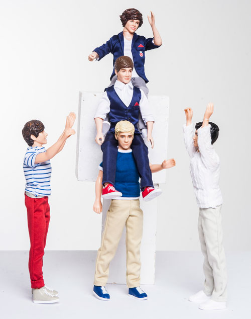Success! Harry, Liam and Niall are a human pyramid while Louis and Zayn watch.