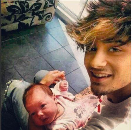 Zayn Malik cuddles a baby